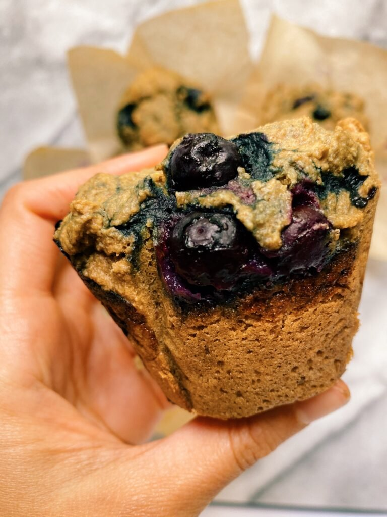 hand holding blueberry muffins